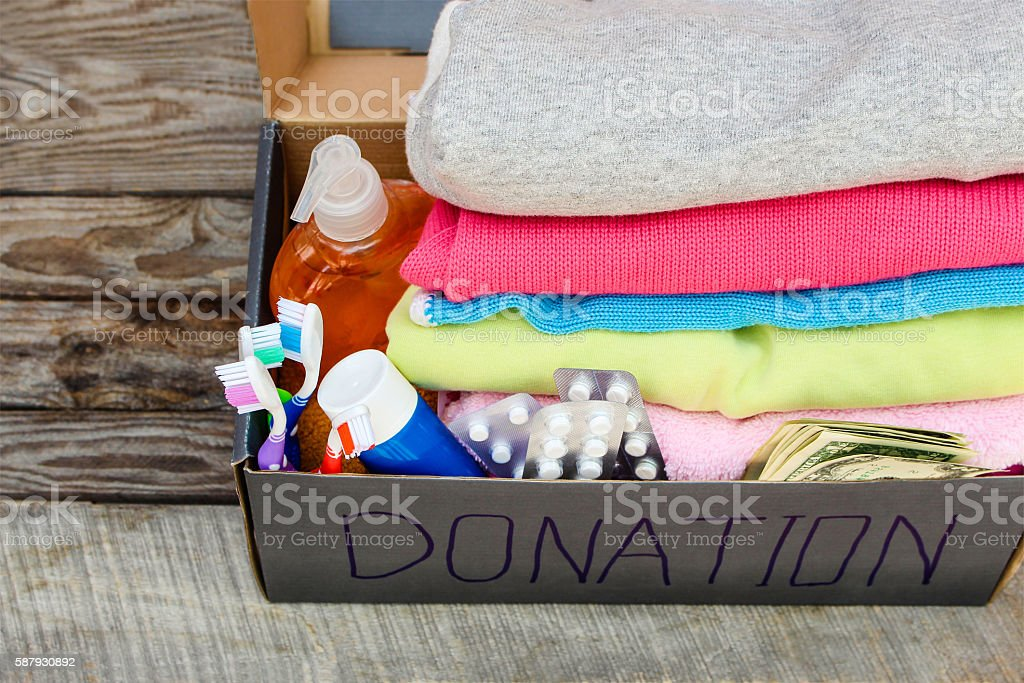 Donation box with clothes, medication, living essentials and money stock photo