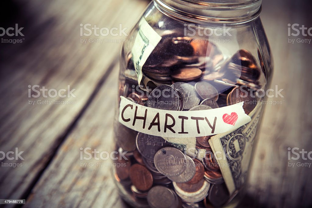 Donation jar of money on rustic wood stock photo