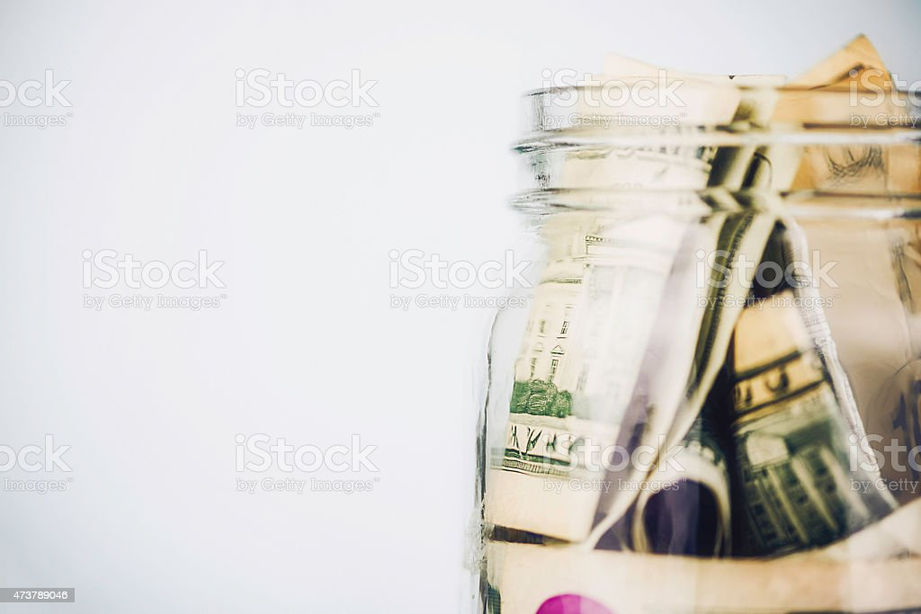 Donation jar overflowing with American money. Fundraising, Savings, Wealth Concepts. stock photo