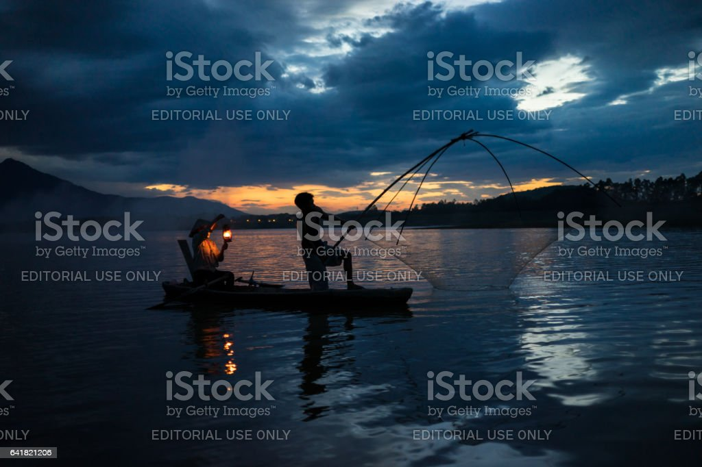 Hanoi, Vietnam - June 12, 2016: Dong Mo lake with a couple of fishers catching fish by net trap in beautiful sunset period in Son Tay town, Hanoi, Vietnam. The wife holding hurricane lamp stock photo