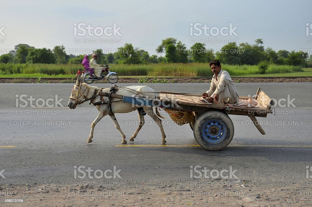 Donkey cart, driver and motorcycle on Pakistan highway royalty-free stock photo