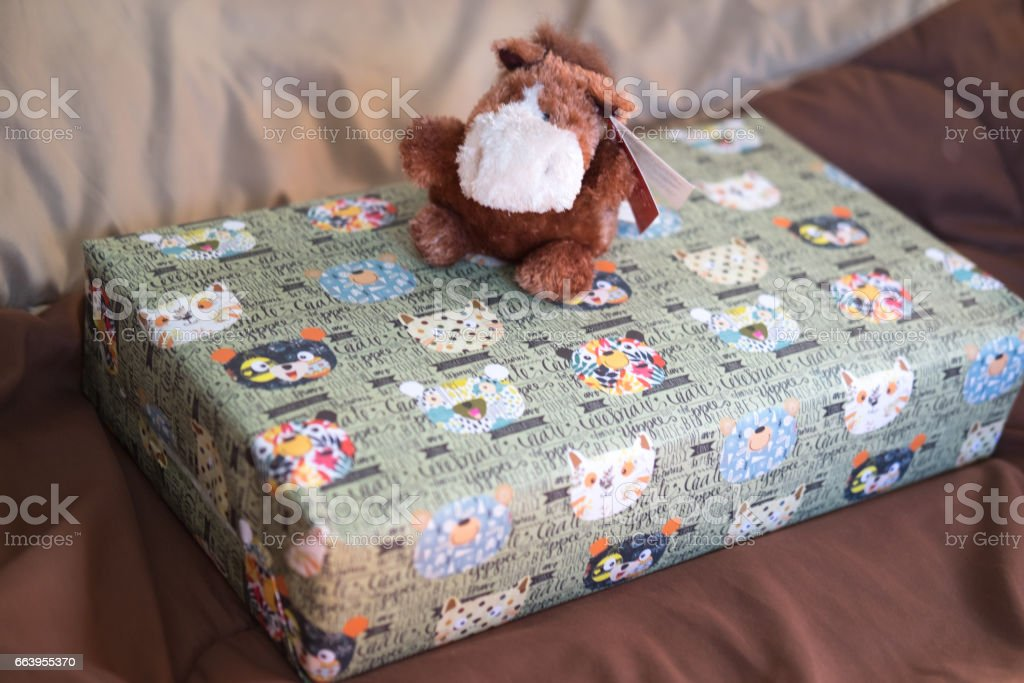 Donkey doll on green gift box, surprise concept stock photo