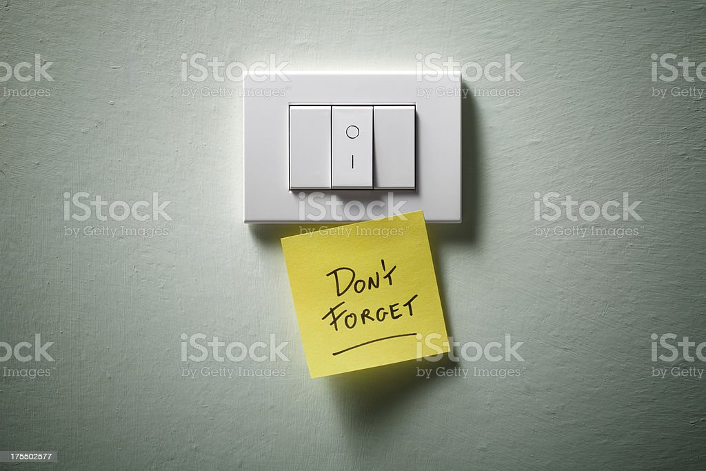 Don't forget. Light switch with yellow sticky note. stock photo