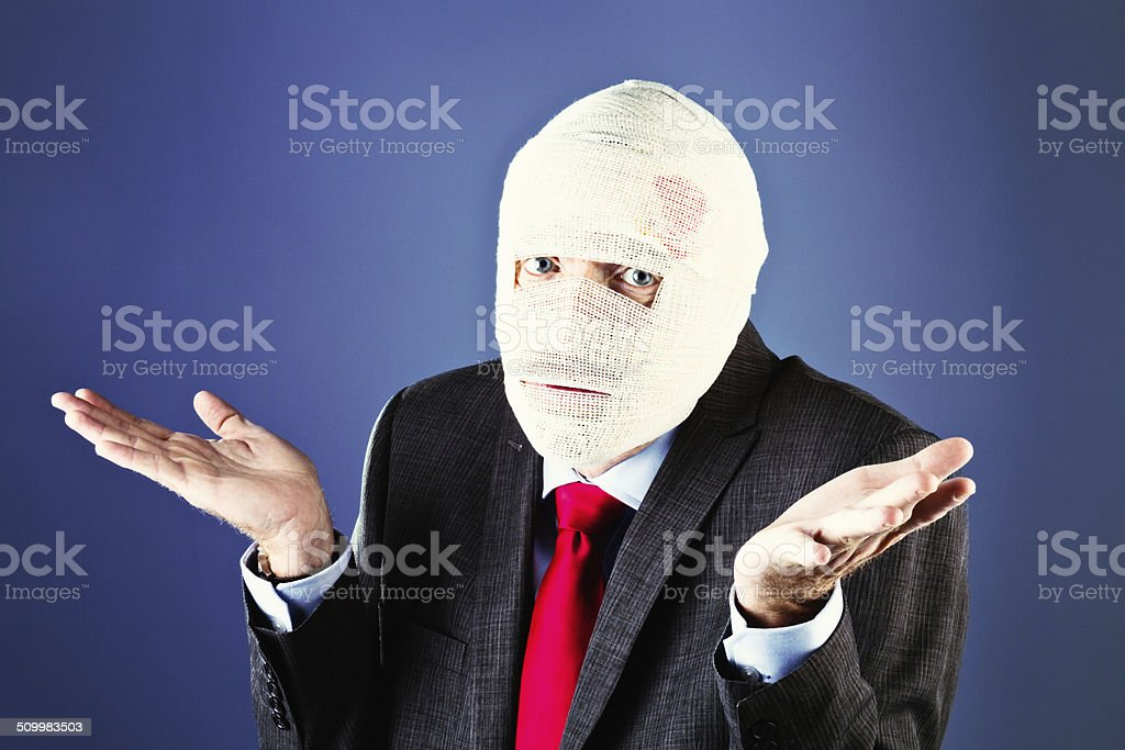 I don't know what happened! Bandaged businessman shrugs helplessly stock photo