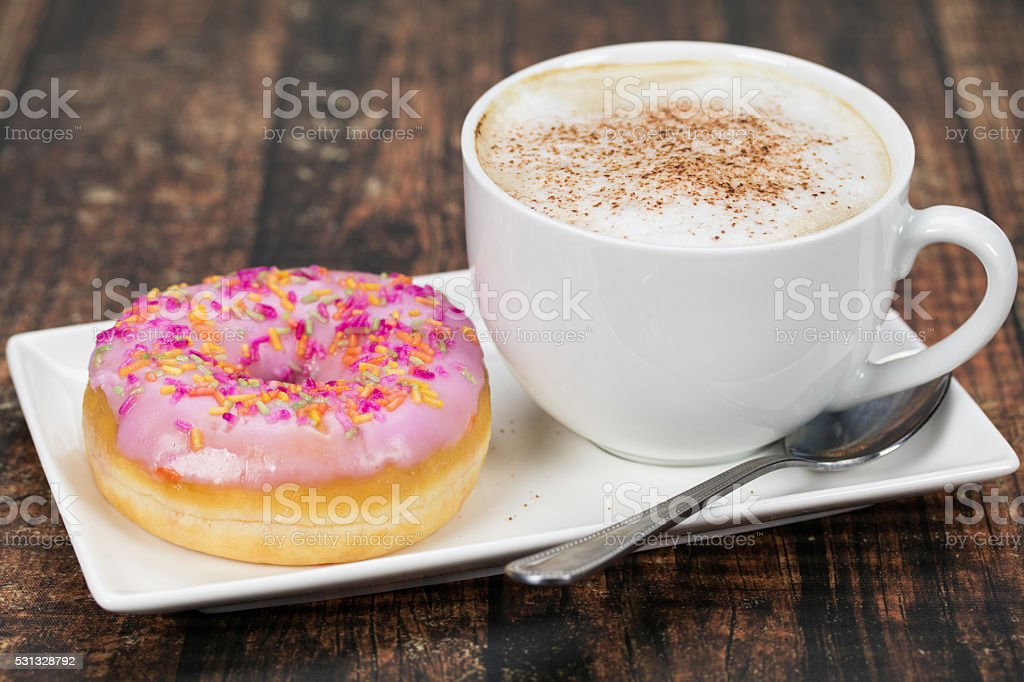 Donut and cappuccino coffee stock photo