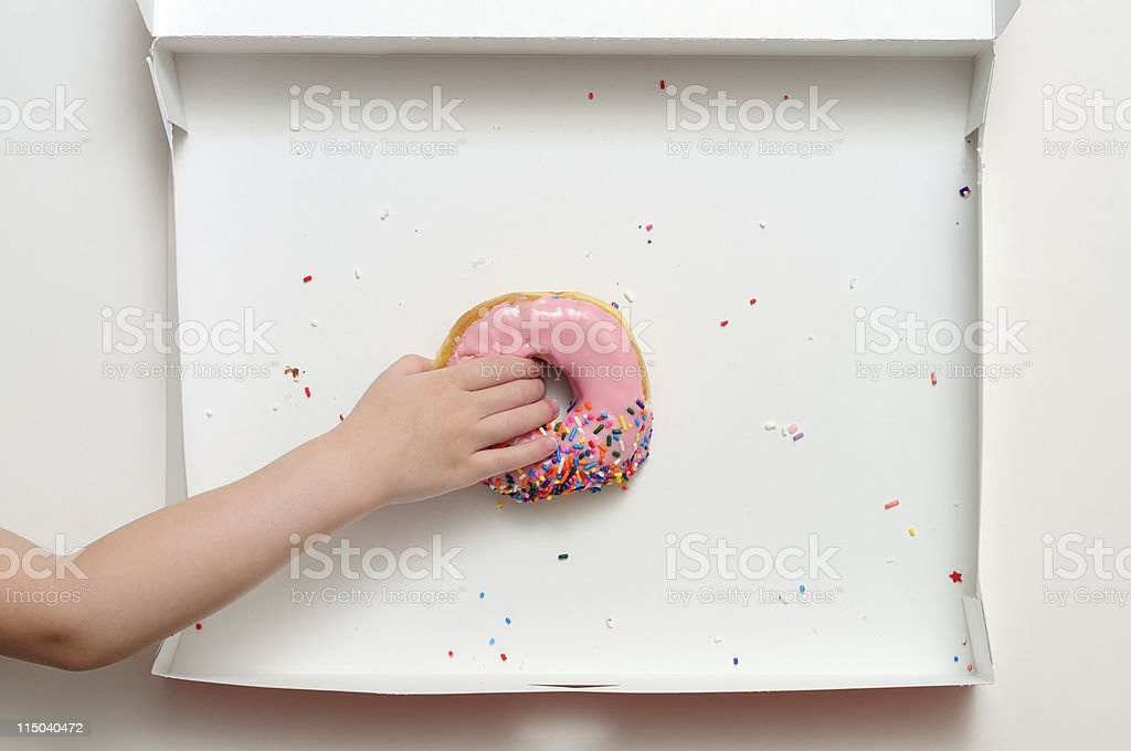 Donut Box with Young Girl's Hand Grabbing Last One stock photo