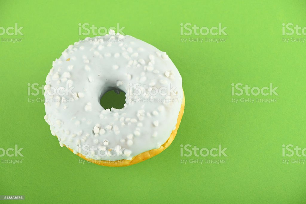 Donut with blue glaze sprinkles on green paper royalty-free stock photo