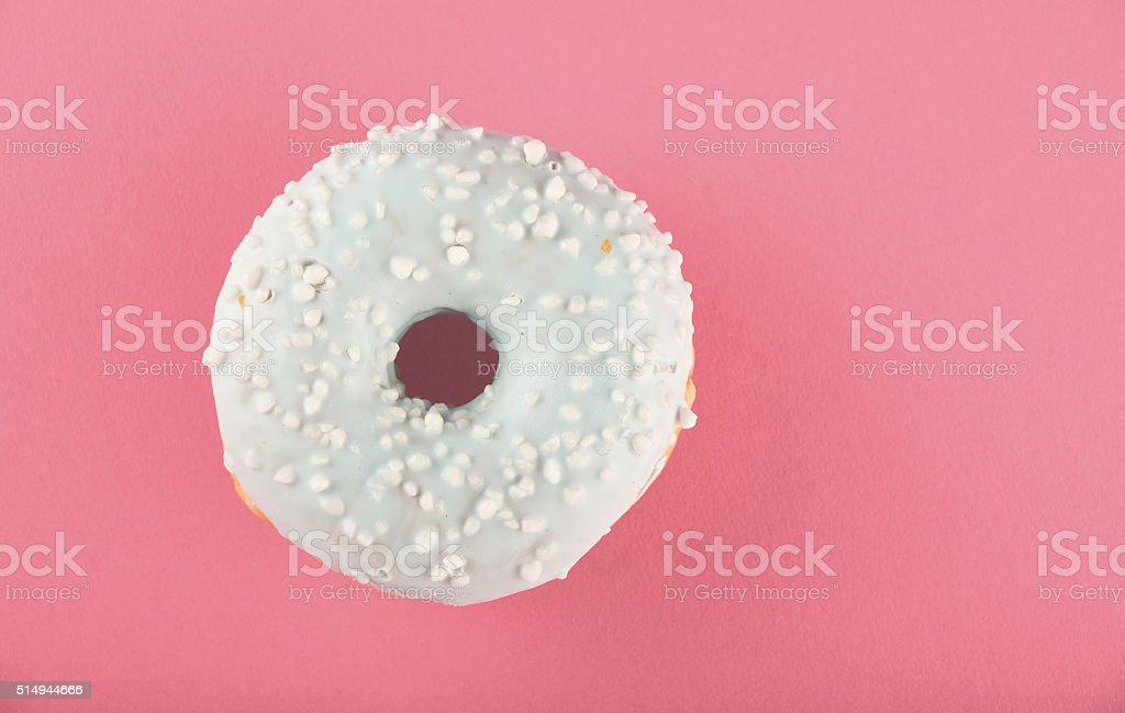 Donut with blue glaze sprinkles on pink paper royalty-free stock photo