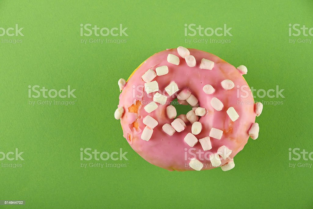 Donut with pink glaze and marshmallow on green royalty-free stock photo