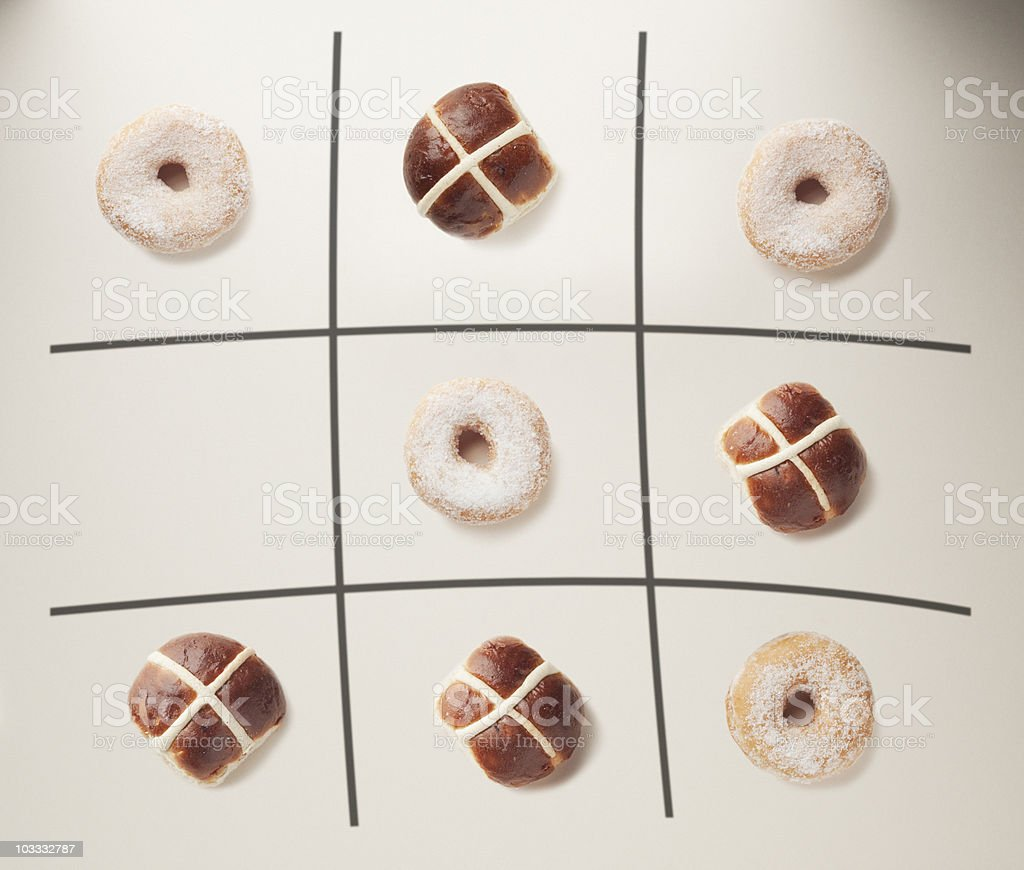 Donuts and hot cross buns on tic-tac-toe grid royalty-free stock photo
