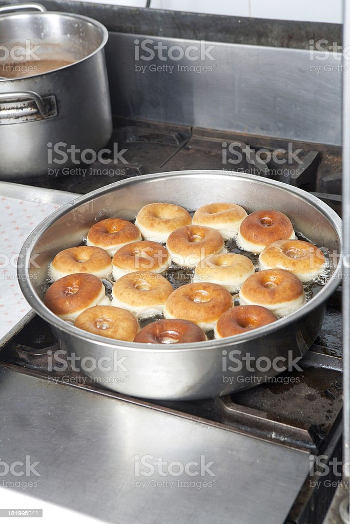 Donuts frying in a pan on the stove royalty-free stock photo
