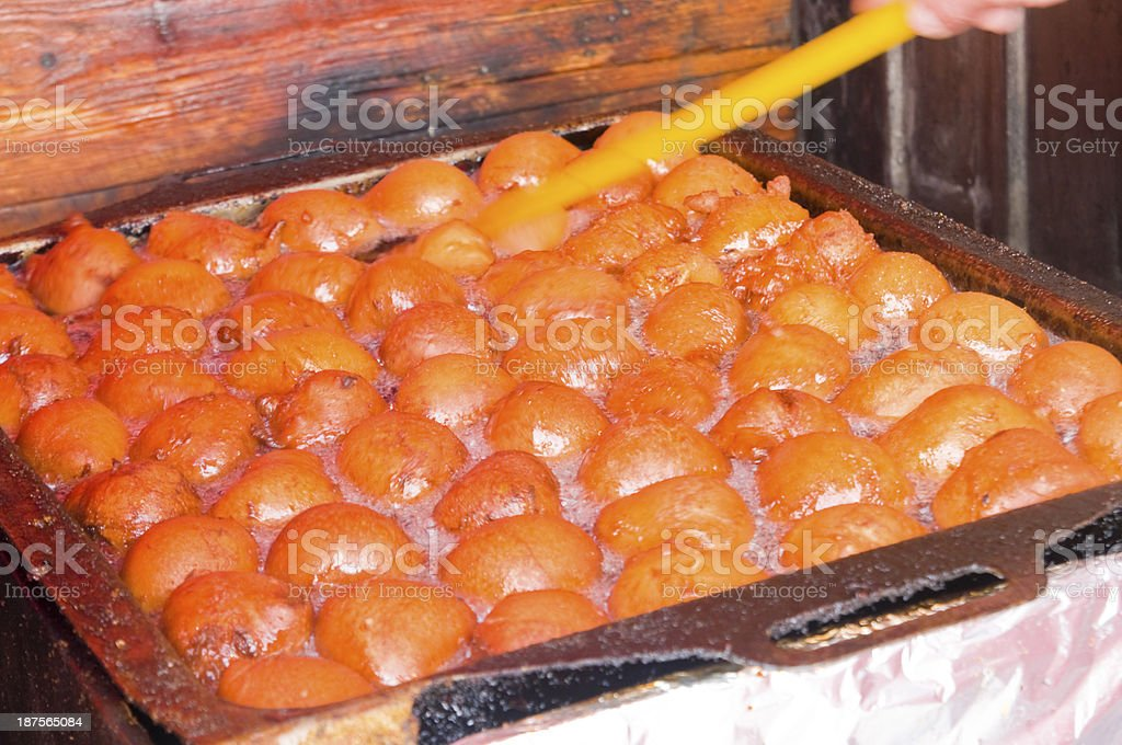 Donuts in hot frying oil stock photo