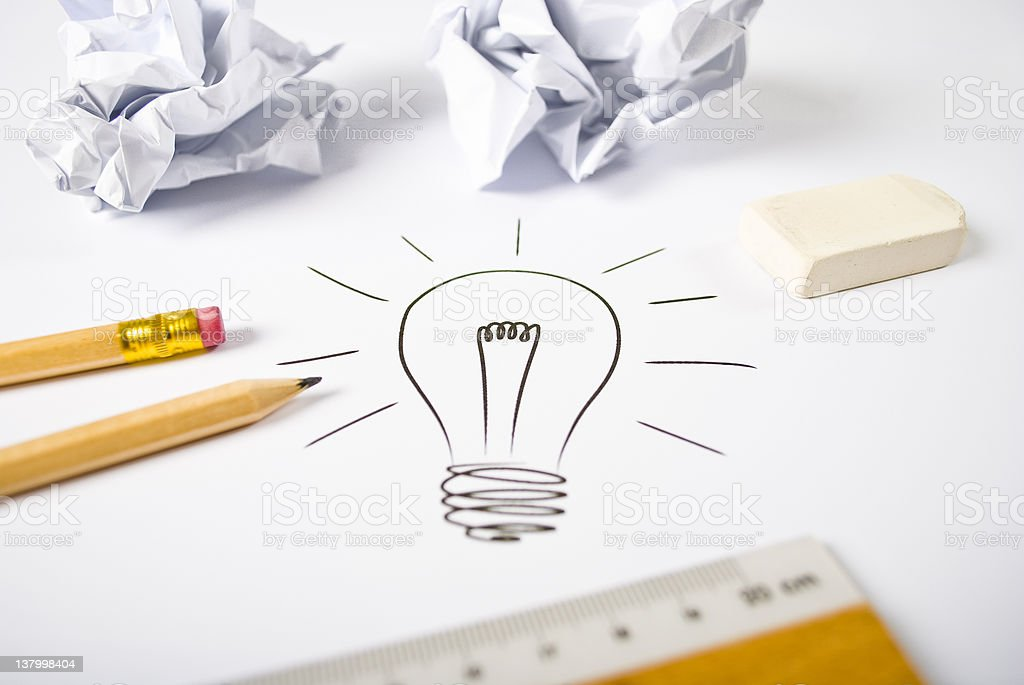Doodle of a light bulb surrounded by pencils and paper stock photo