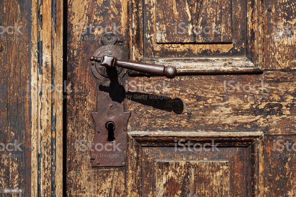 Door handle on an antique wooden door stock photo