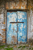 Door in an ancient building locked with small rusty padlock