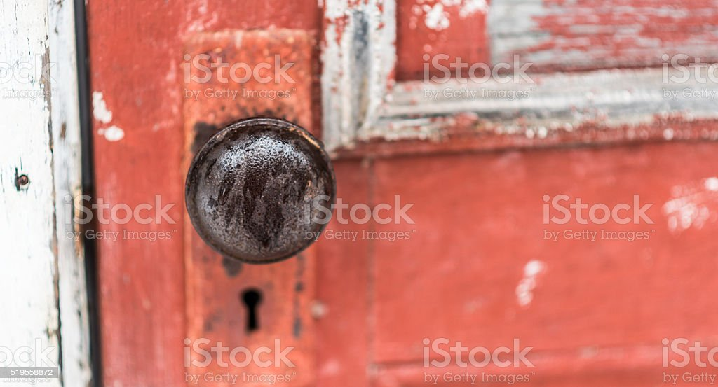Door knob with skeleton keyhole on old paint chipped, door. stock photo