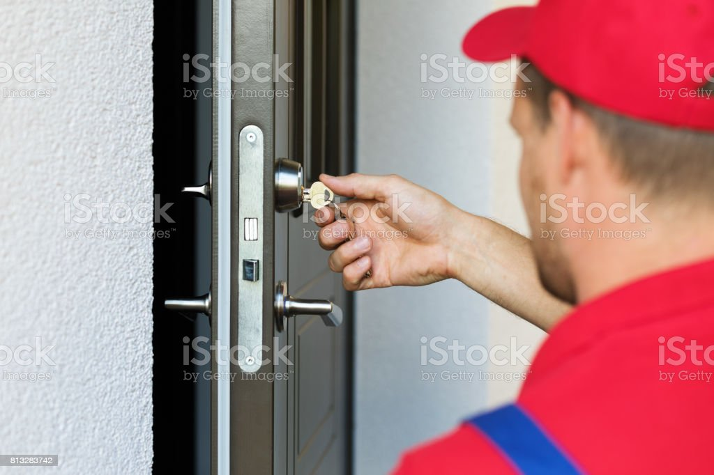door lock service - locksmith working in red uniform stock photo