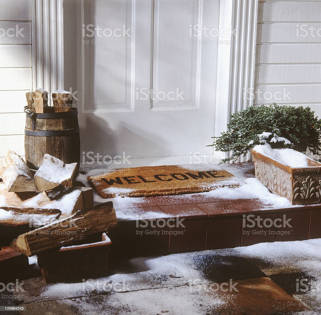 door of house with welcome mat in winter stock photo