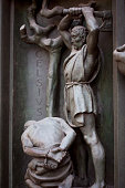 Door of the duome, Milan, executioner executes human. Bronze bas