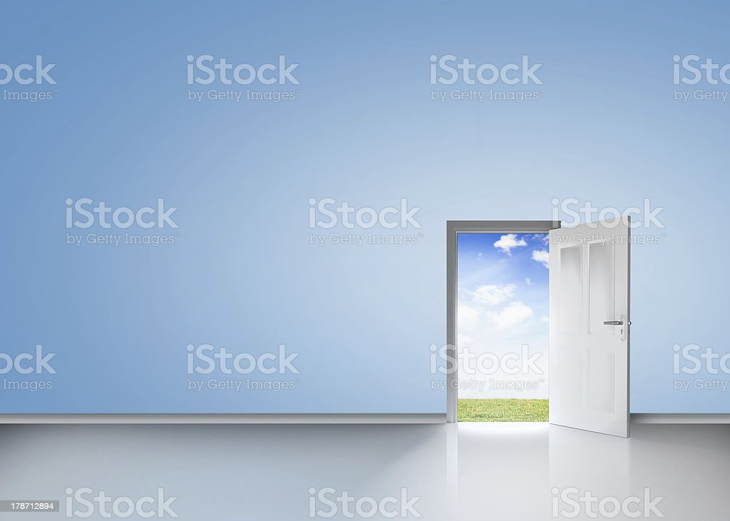 Door opening to reveal blue sky and meadow stock photo