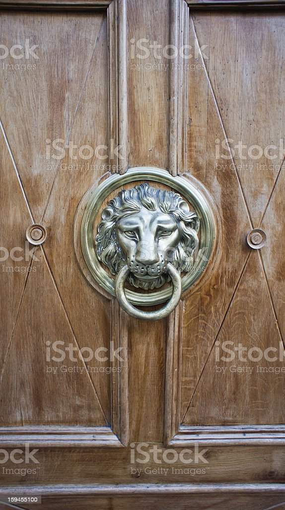 Door with ancient style carved lion head knocker royalty-free stock photo