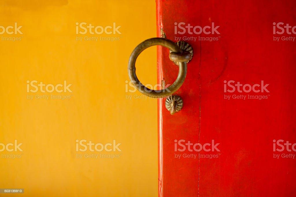 Doorhandles of red door against a yellow background stock photo