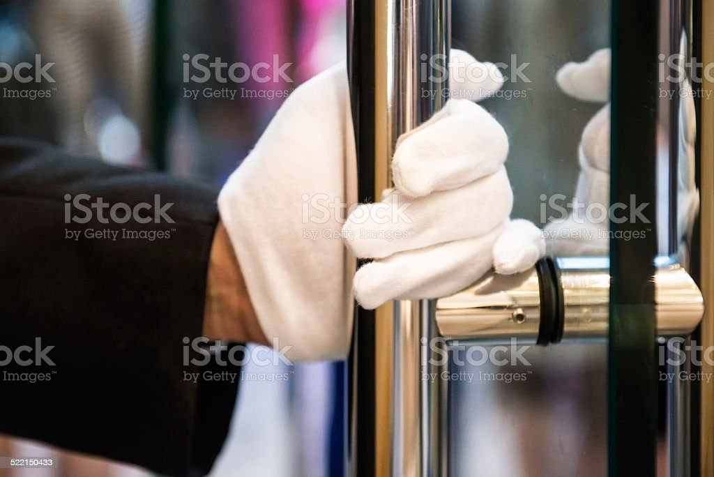 Doorman with White Gloves Opening Door at Luxury Shopping Mall stock photo