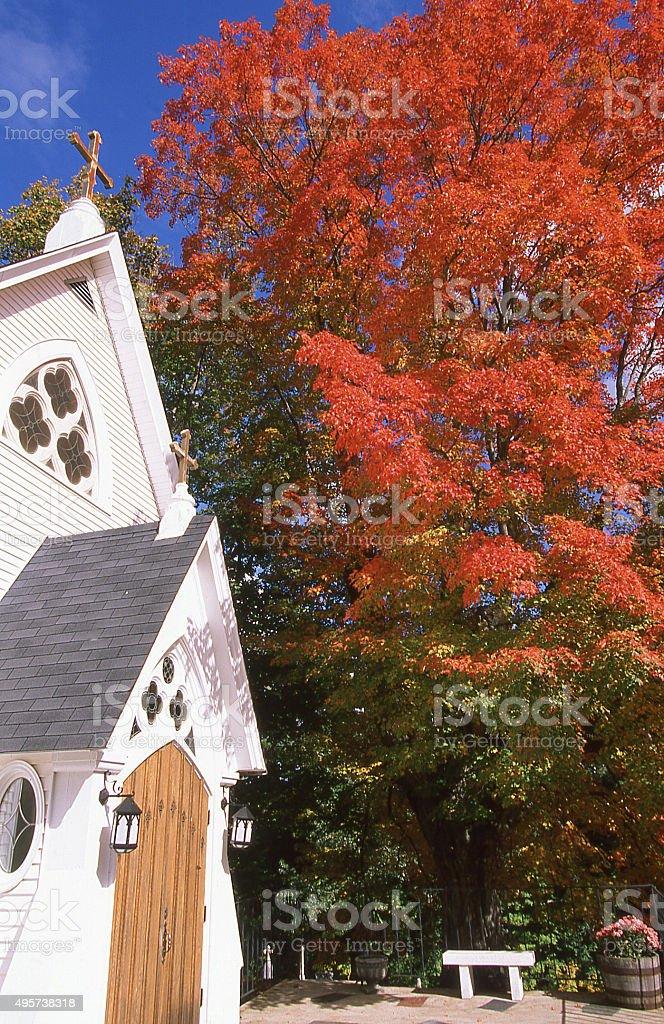 Doorway bench white chapel red maple leaves autumn Gloucester Massachusetts stock photo