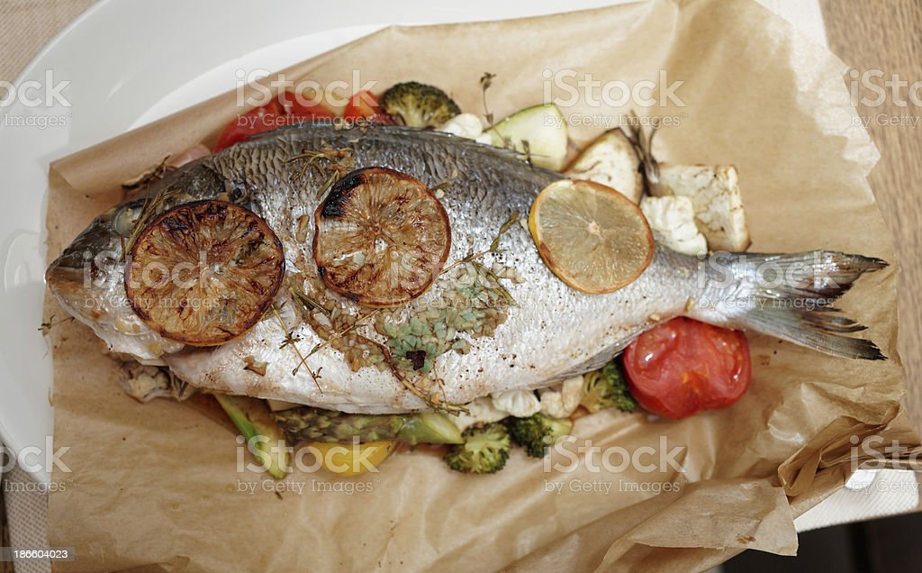 Dorade roasted in paper with vegetables royalty-free stock photo