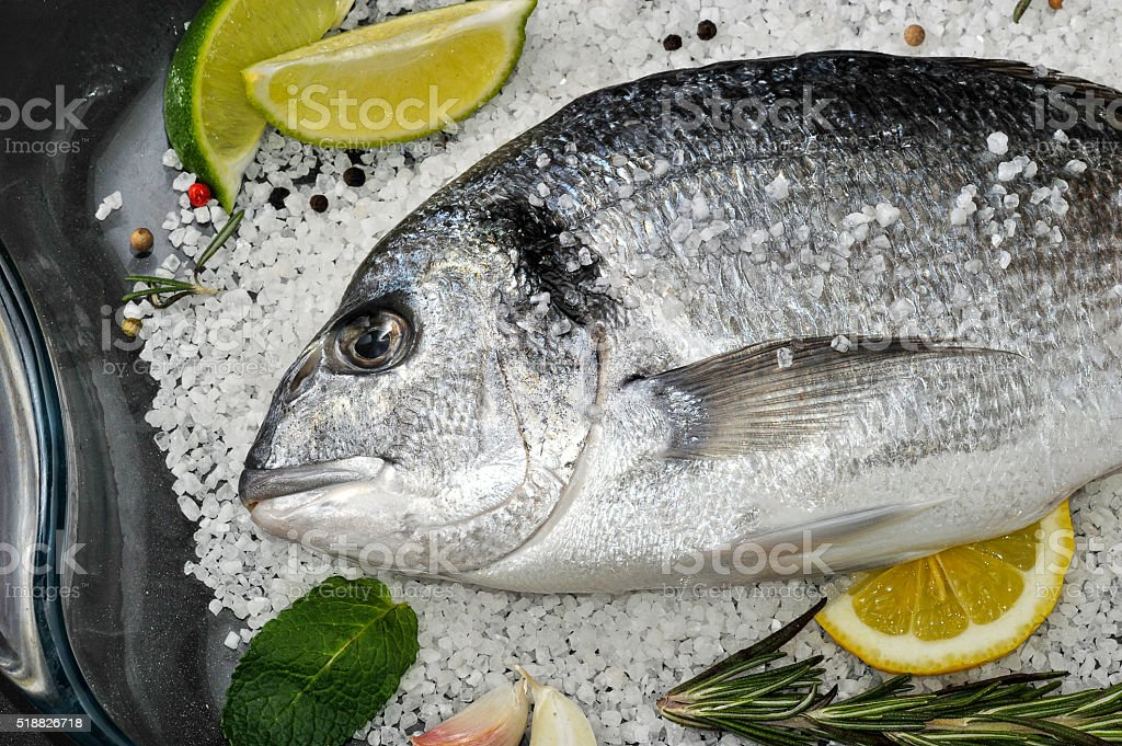 Dorado fish is in glass dish with salt, rosemary, garlic stock photo