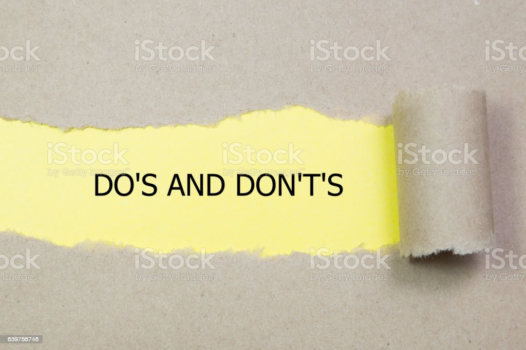 Do's and Don't's Message written under torn paper. stock photo