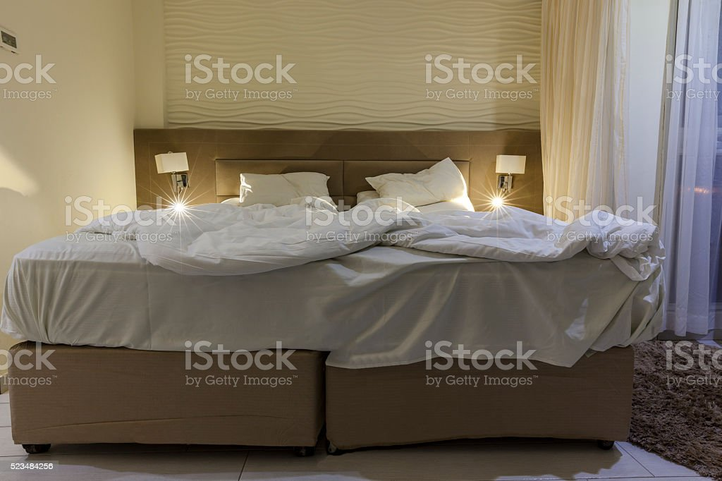 Double bed hotel room with messed bed reading light stock photo