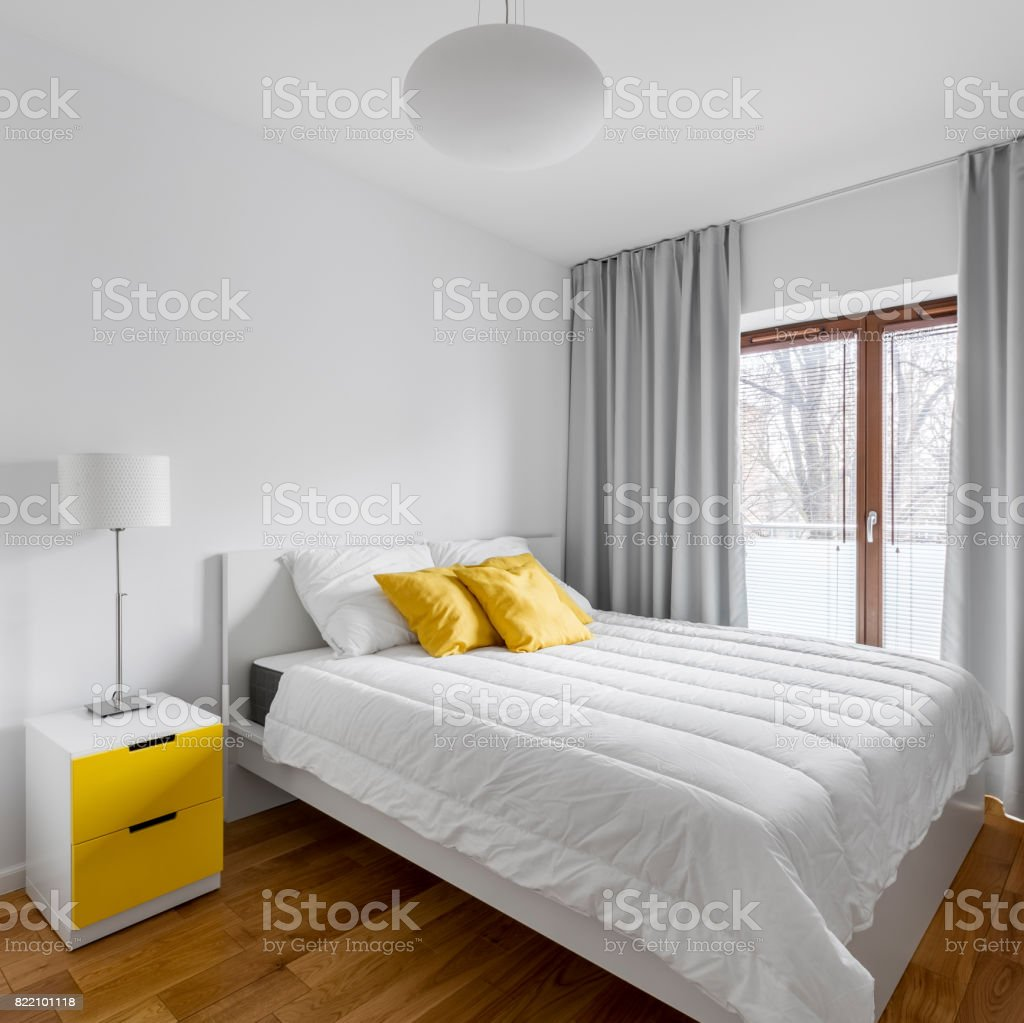 Big double bed in white and yellow home bedroom