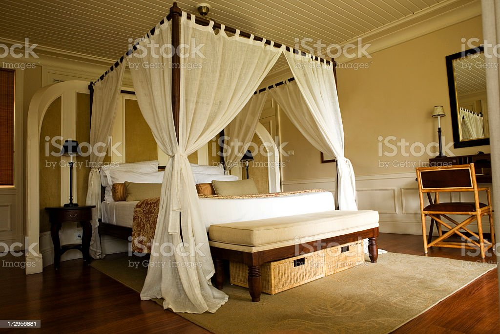 Double bed with white curtains stock photo