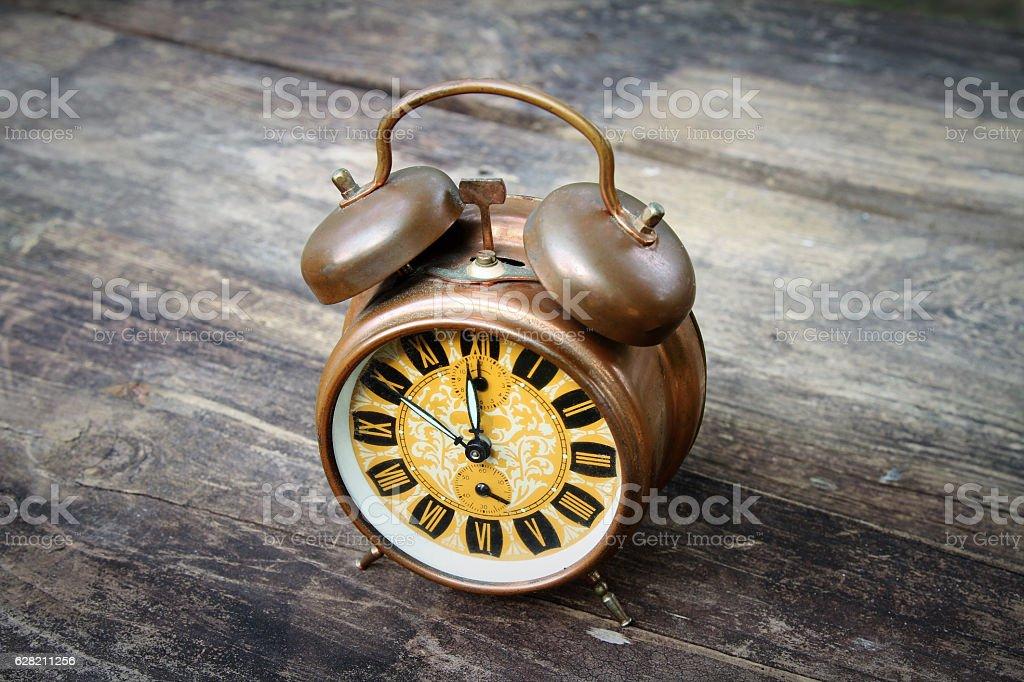 Double bell antique alarm clock on dark wood table stock photo
