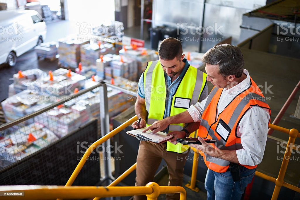 Double checking their shipping schedule stock photo