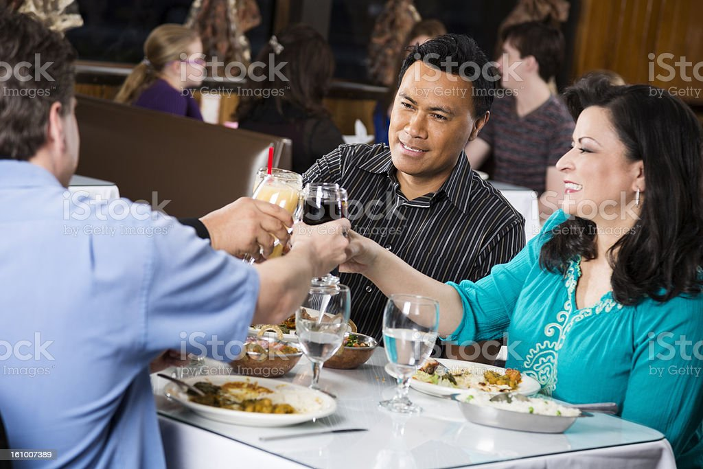 Double date at a restaurant raising glasses in toast stock photo