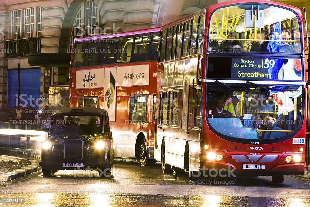 Double decker buses and taxi cab in London at night royalty-free stock photo