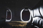 Double exposure, Airplane window with seat and night sky