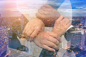 Double exposure business group with hands together