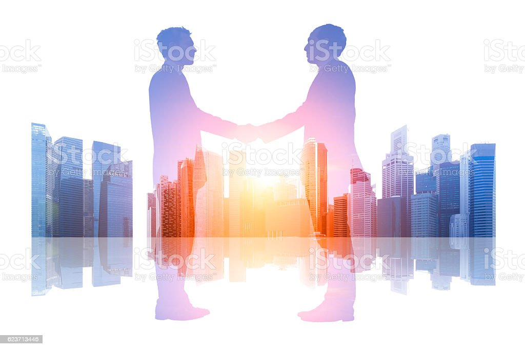Double exposure business people shaking hands over a cityscape background stock photo