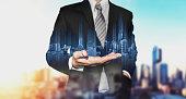 Double exposure businessman holding blue city hologram