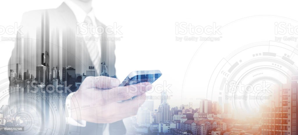 Double exposure businessman using smartphone and city in sunrise, with white copy space stock photo