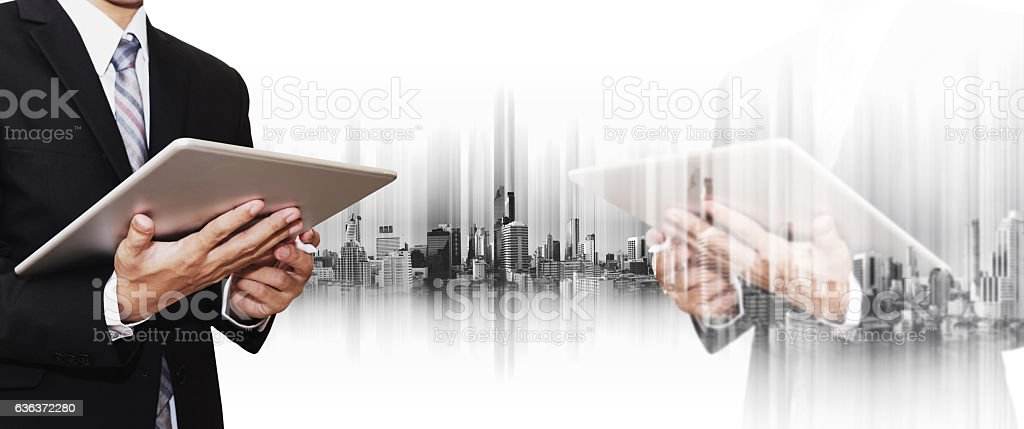 Double exposure businessman using smartphone and digital tablet with city stock photo