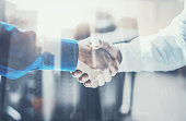 Double exposure concept.Close up view of business partnership handshake