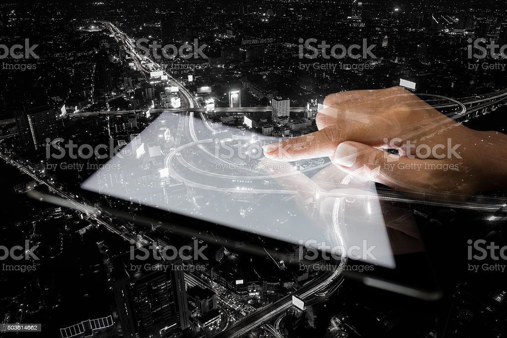 double exposure hand using tablet and city on night background stock photo