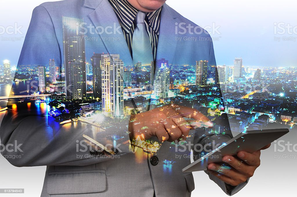 Double exposure of a businessman and city using a tablet stock photo