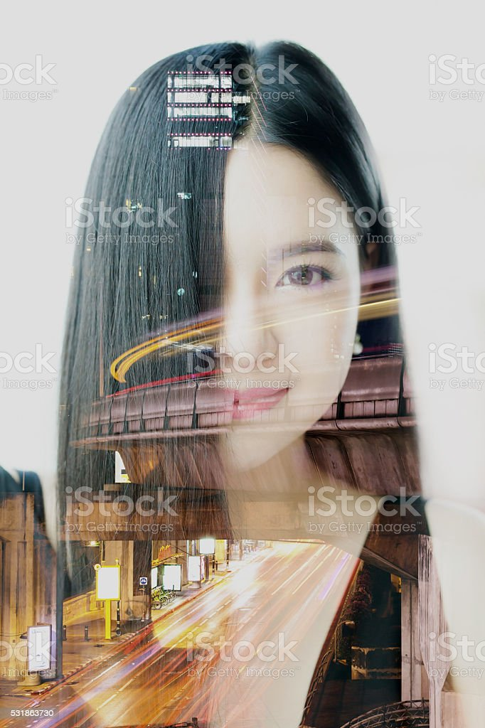 Double exposure of Asian woman dissolved with night cityscape stock photo