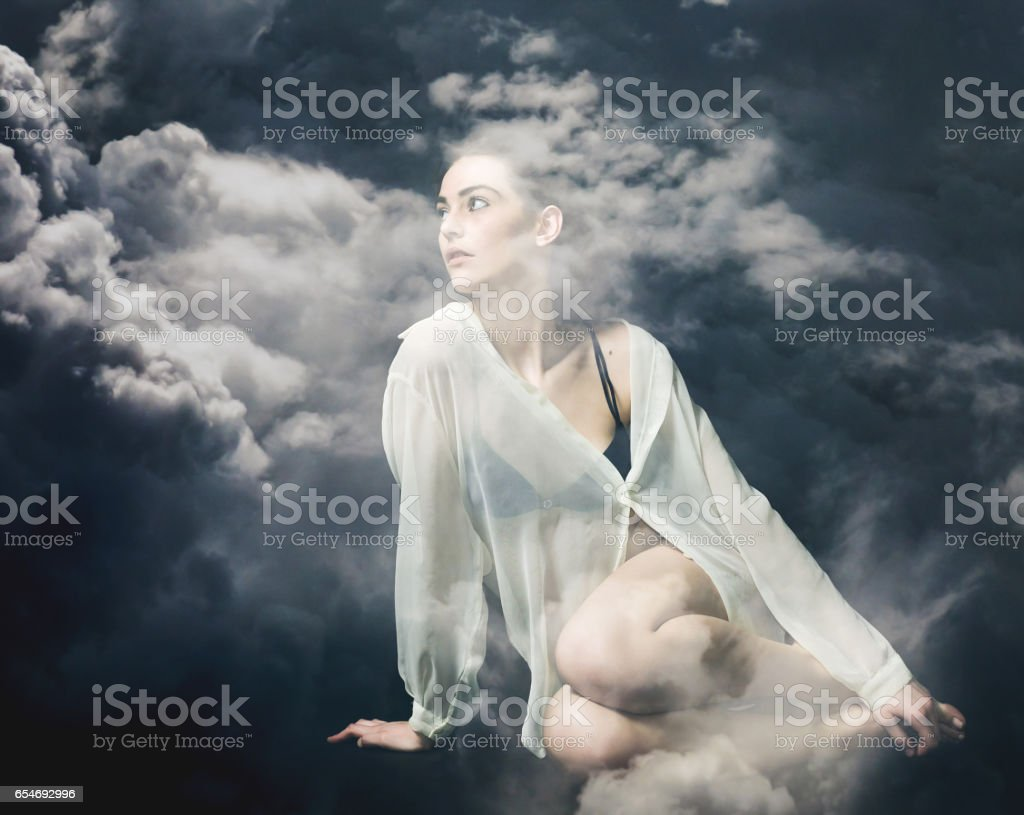 Double exposure of beautiful and thoughtful girl and stormy cloudscape stock photo
