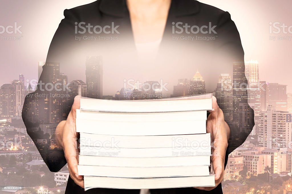 Double exposure of business holding a books with night cityscape stock photo